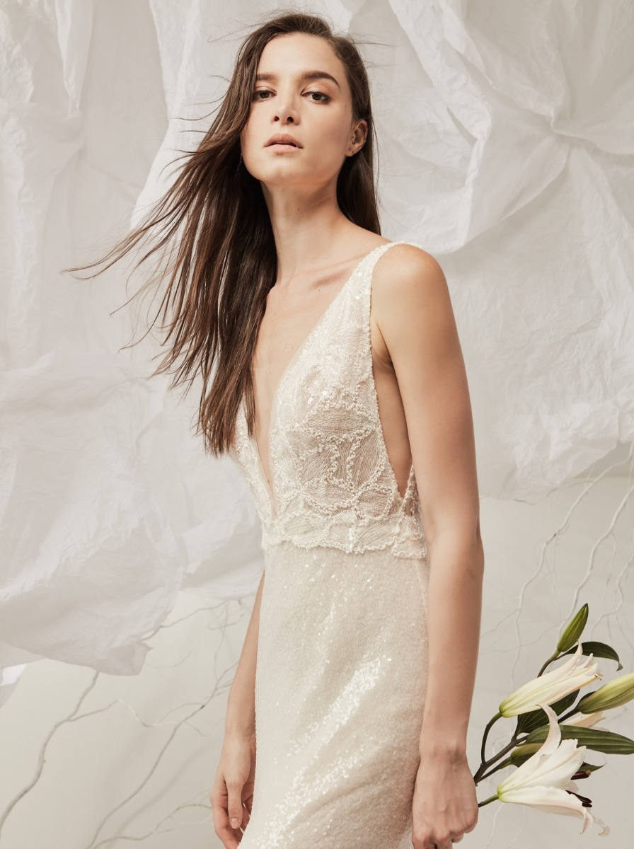 Mermaid wedding dress with a plunging, V-neckline bodice in embroidered tulle with low armholes. Fitted skirt crafted in sequin fabric.