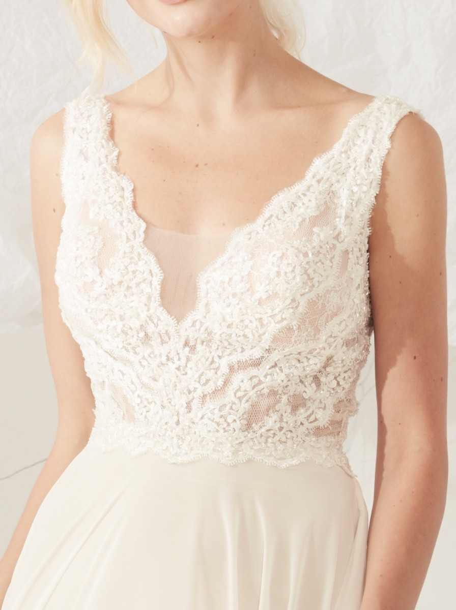 Flowing A-line wedding dress in chiffon with beaded lace bodice and V-neckline.