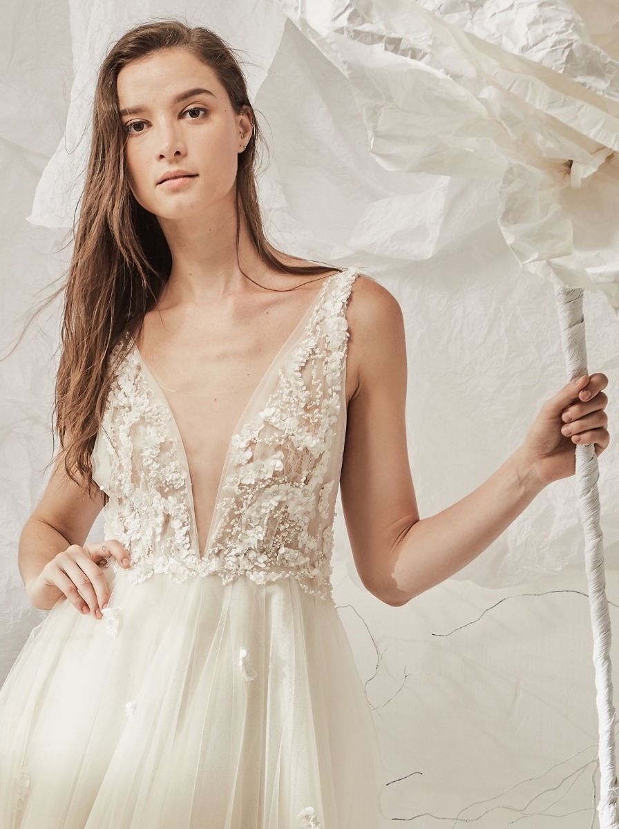 A-line wedding dress with shimmering pearl beads and small flowers over a plunging V-neckline lace bodice.