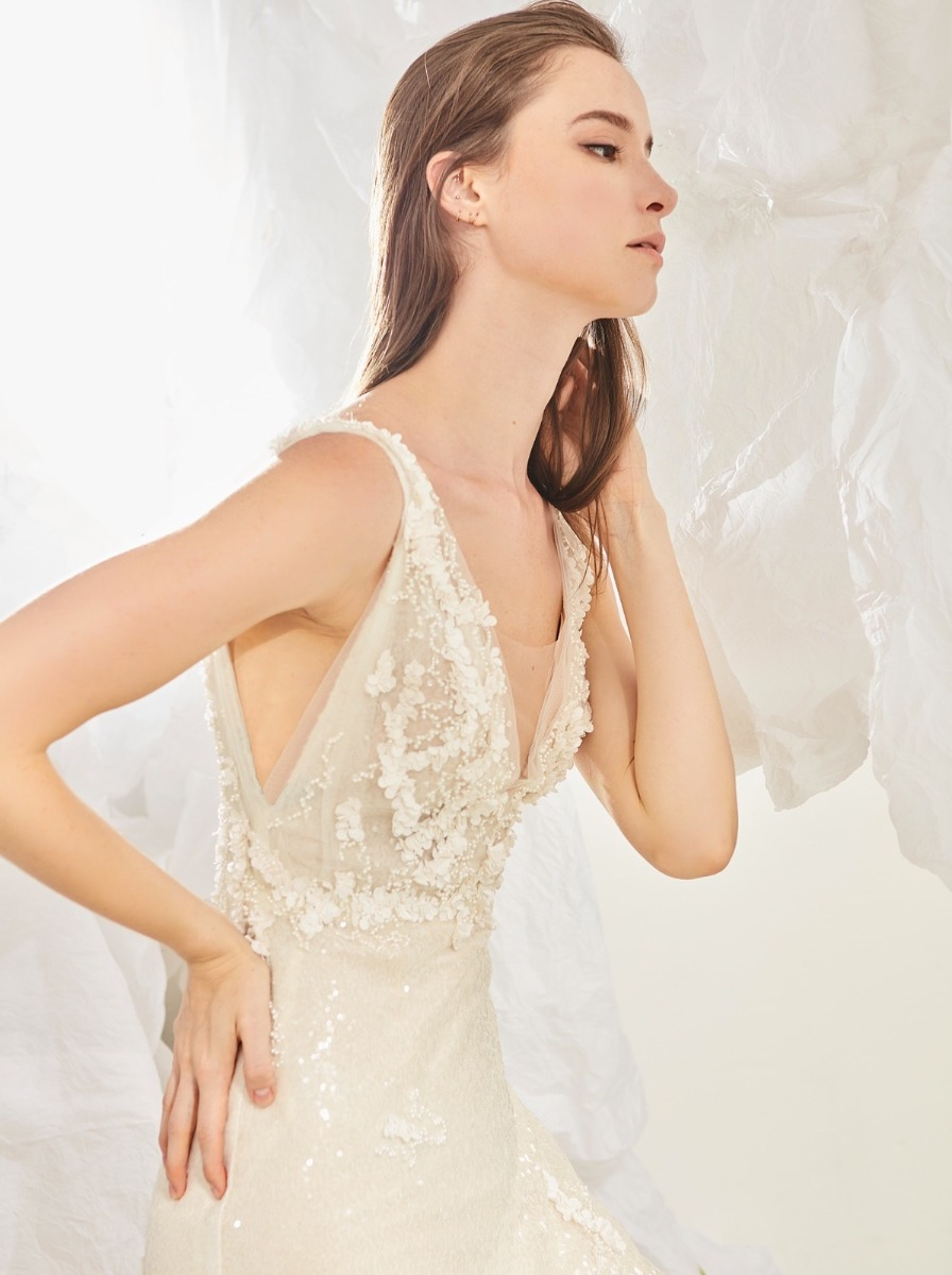 Mermaid wedding dress in micro-sequin fabric with pearl beads and small flowers over V-neck bodice with low armholes.
