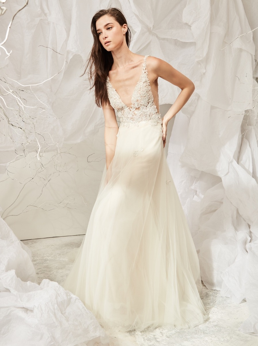 A-line wedding dress crafted in tulle with delicate appliques over illusion bodice with low armholes.