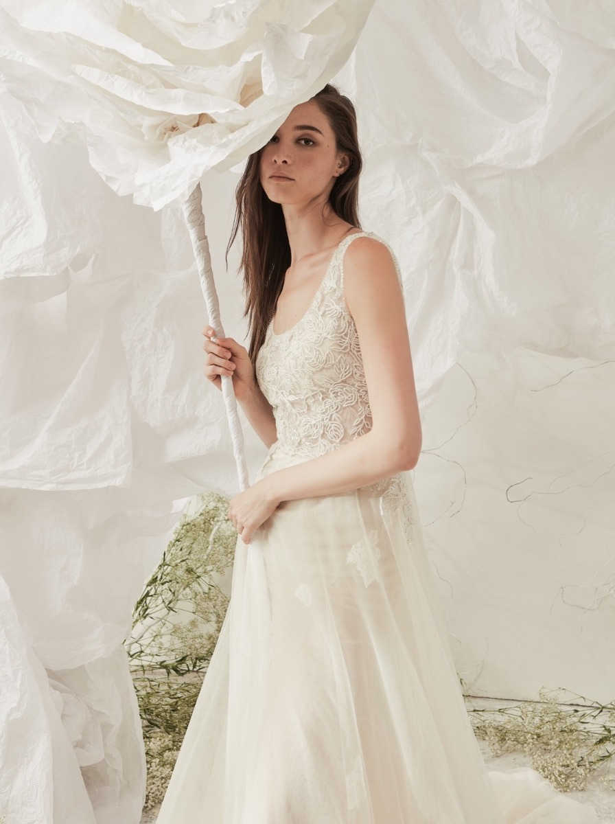A-line wedding dress in tulle with ivory floral appliques over a scoop neck bodice.