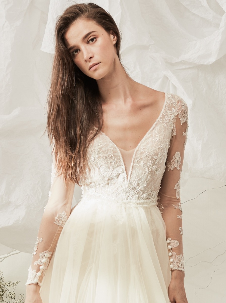 A-line wedding dress with beaded small flower over a plunging V-neckline lace bodice with illusion long sleeves.