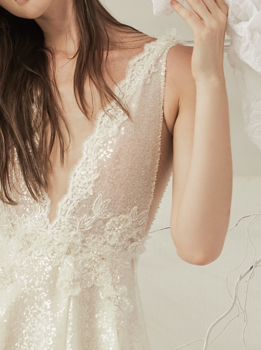 Voluminous princess wedding dress crafted in glistening sequin fabric. Bodice with scallop lace edge detailing along the V-neck with beaded ice flowers at the waist.