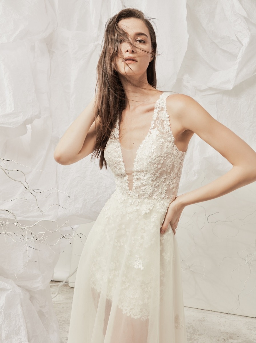 Plunging V-neck short wedding dress with cascades of embroidered flowers and illusion tulle overlay on the skirt.