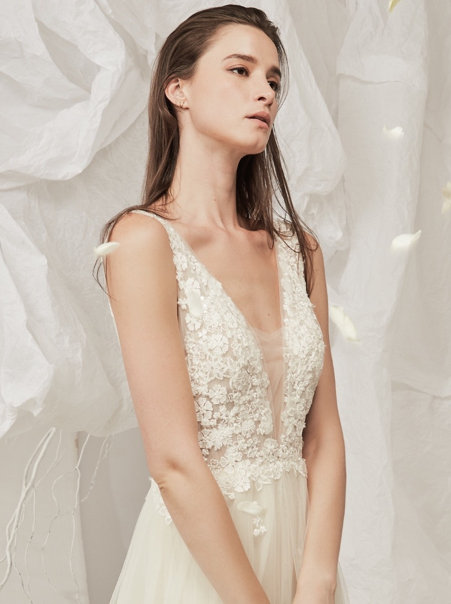 Flowing A-line wedding dress in soft tulle with embroidered flowers over a plunging V-neckline bodice.