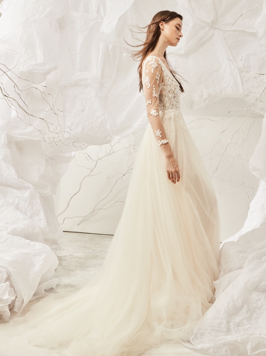 Flowing A-line wedding dress in soft tulle with embroidered flowers over a plunging V-neckline bodice with tattoo-effect long sleeves.