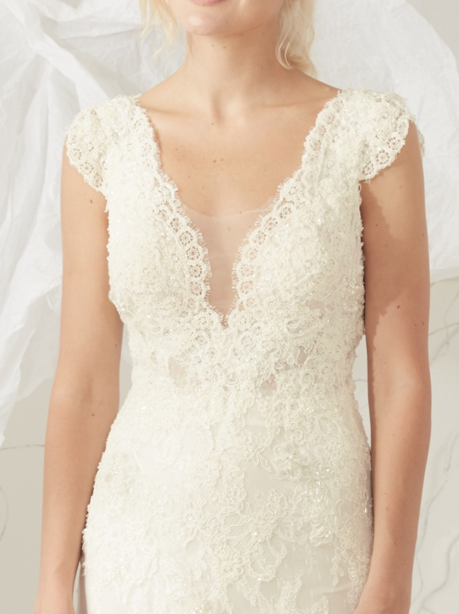 Mermaid wedding dress in lace with scalloped V-neckline and cascades of beaded lace appliqués and 3D ice flowers.