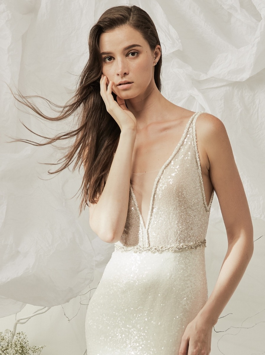 Mermaid wedding dress crafted entirely in micro-sequin fabric with silver embroidery along the plunging V-neckline with beaded appliques at the waist.