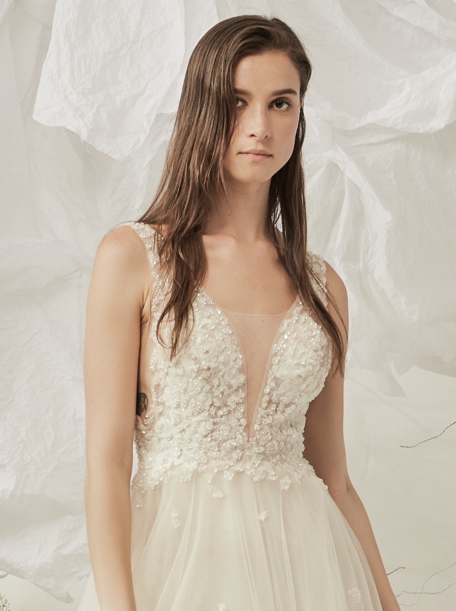 A-line wedding dress in tulle with glistening sequined motifs over a plunging V-neckline bodice with low armholes.