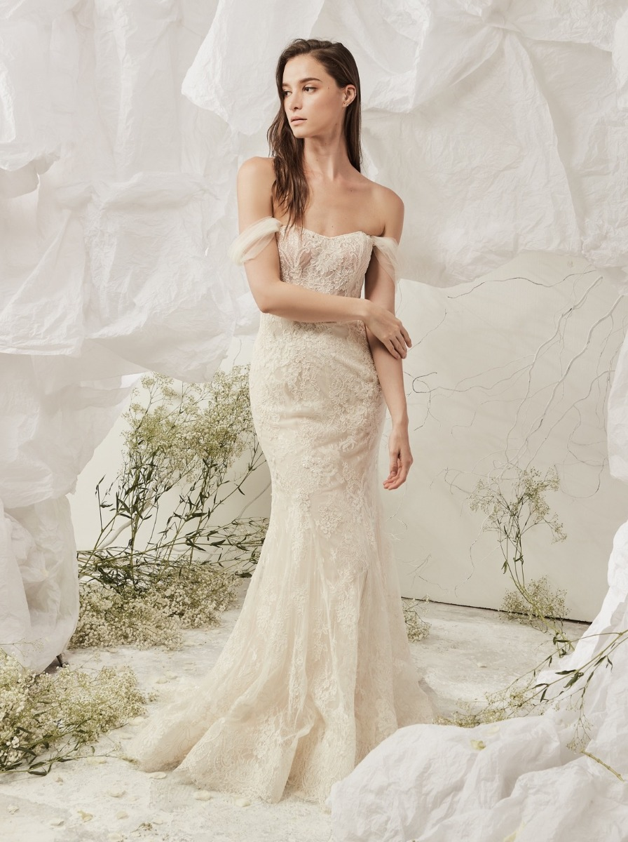 Mermaid wedding dress in lace with a built-in corset bodice adorned and detachable off-shoulder tulle sleeves. Delicate lace placements and beaded floral appliques are adorned along the skirt for added sparkles.