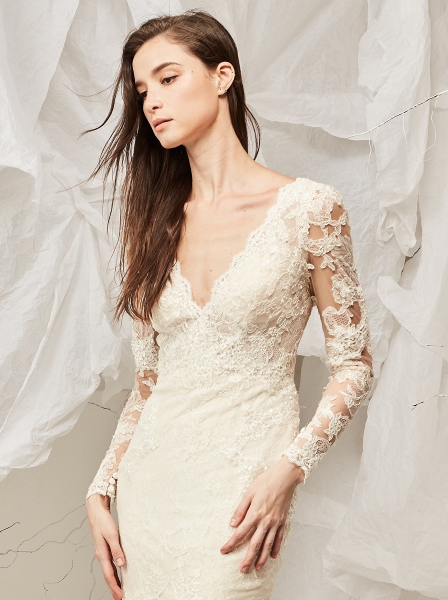 Mermaid wedding dress crafted in lace with a V-neckline bodice adorned cascades of beaded appliques. Long sleeves in illusion, creates a magnificent tattoo-effect.