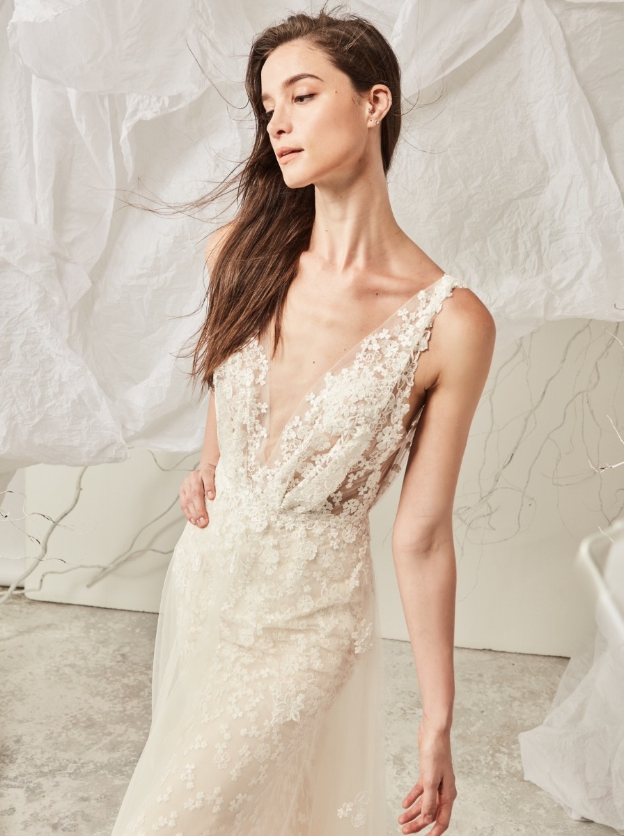 Mermaid wedding dress crafted in tulle with embroidered small flowers over illusion bodice. Fitted skirt with tulle overlay.