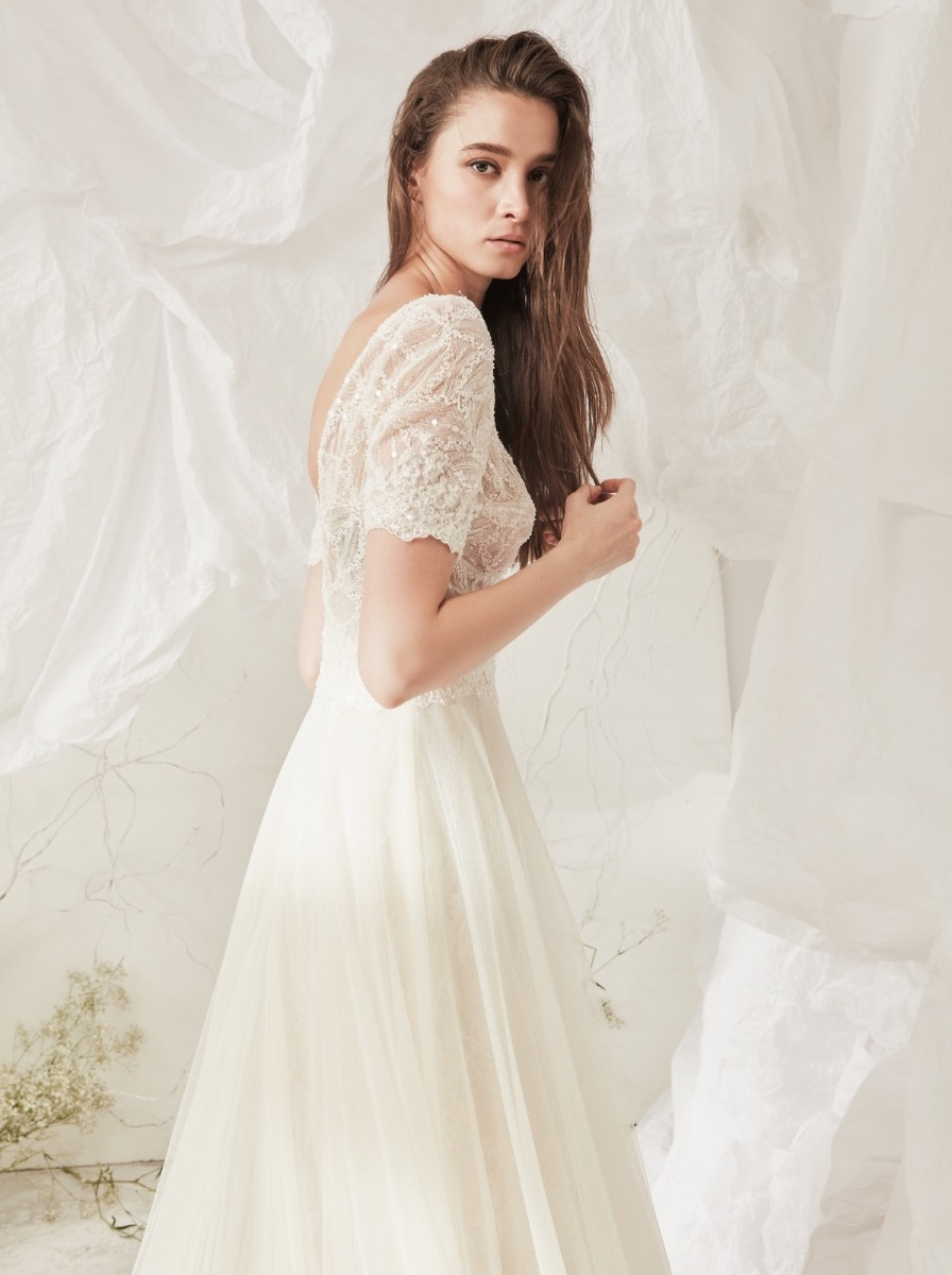 A-line tulle wedding dress with embroidered tulle bodice adorned with strips of shimmering sequins. Short sleeves and waist with beaded lace detailing.