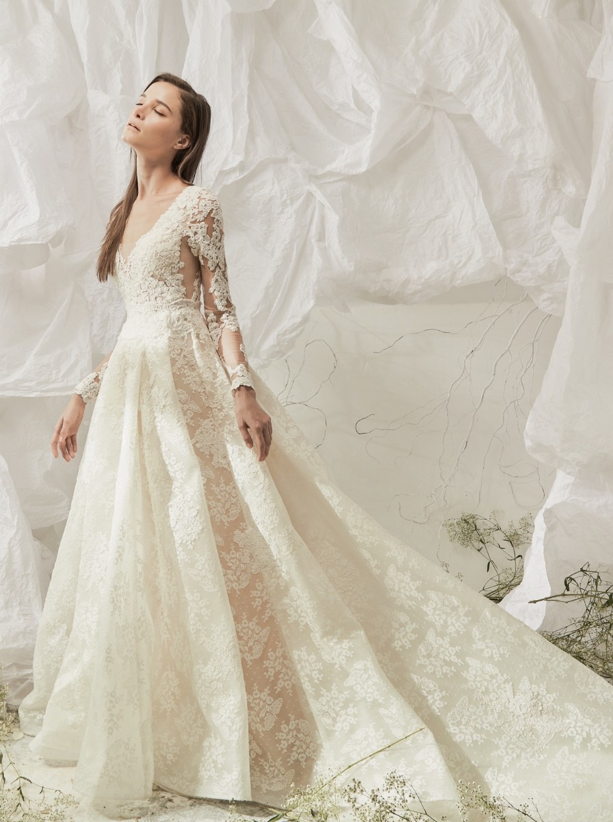 Princess wedding dress in exquisite lace with floral appliques over a V-neck illusion bodice with tattoo-effect long sleeves.