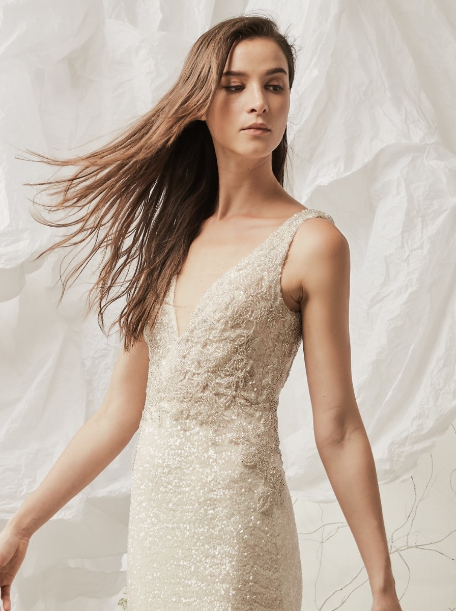 Mermaid wedding dress in micro-sequin fabric with silver beaded appliques over a V-neckline bodice.