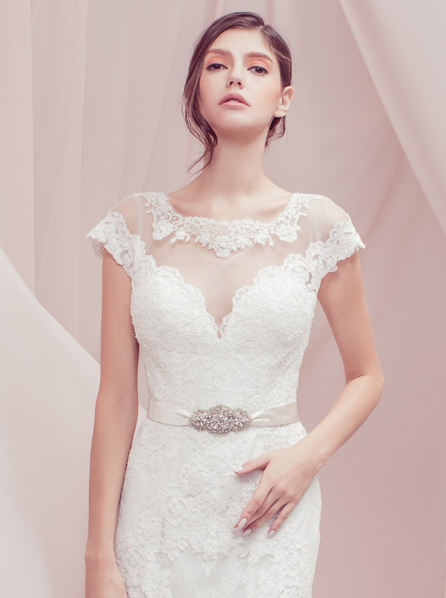 Mermaid wedding dress in lace with illusion neckline and cap sleeves adorned with floral lace appliques on the bodice. Sparking gemstone applique and satin around the waist, creates a waist-defining bridal style with its belt-effect design.