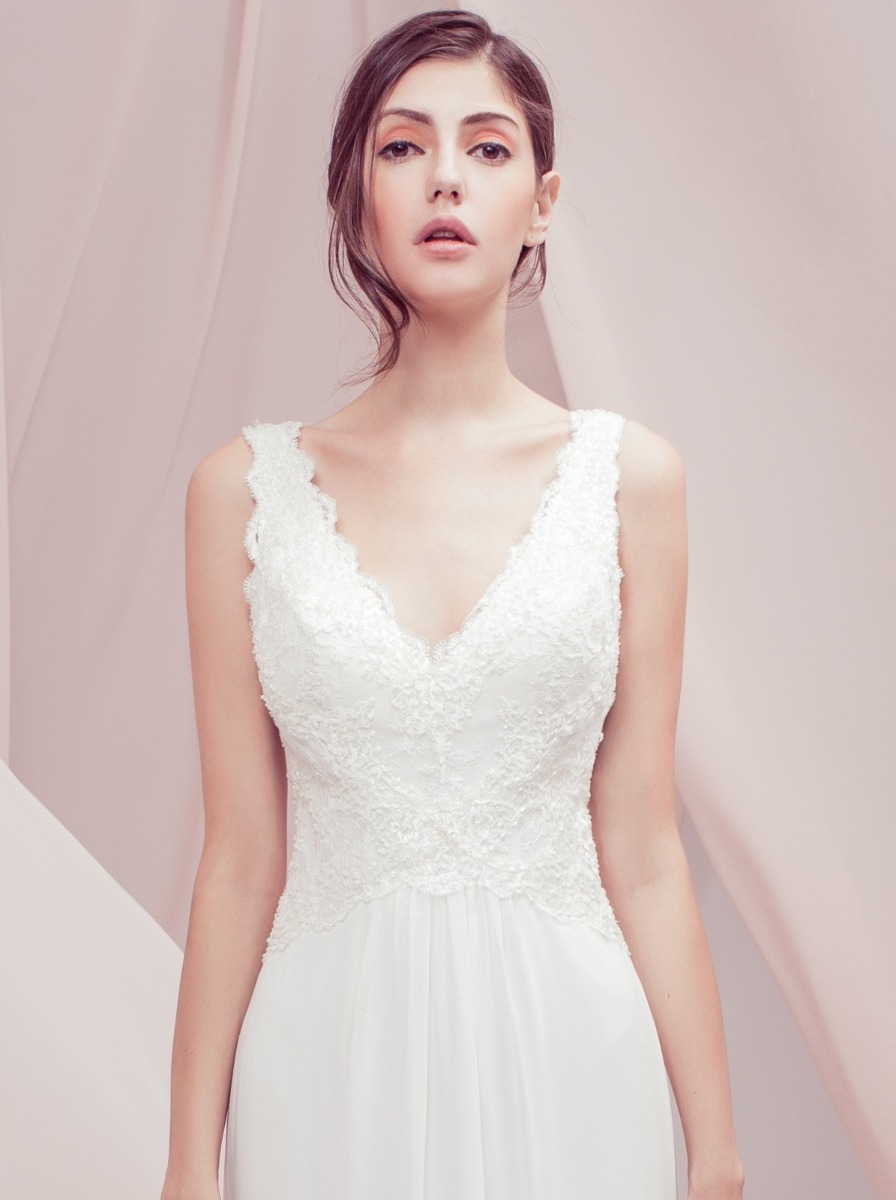 Romantic sheath wedding dress in chiffon with a beaded lace bodice and scalloped lace edge along the V-neckline and back. Chiffon skirt with lace trim at the hem of the skirt.