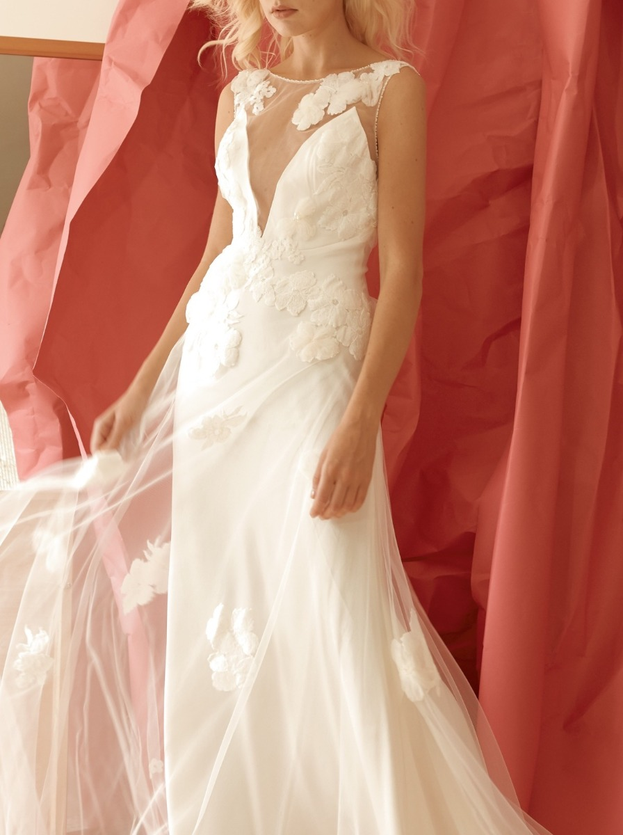 Column wedding dress in tulle with a plunging, illusion V-neckline bodice adorned with cascades of romantic floral appliques.
