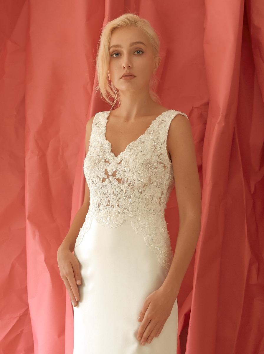 Column wedding dress with shimmering beads and floral lace appliques over an illusion bodice with crepe skirt.