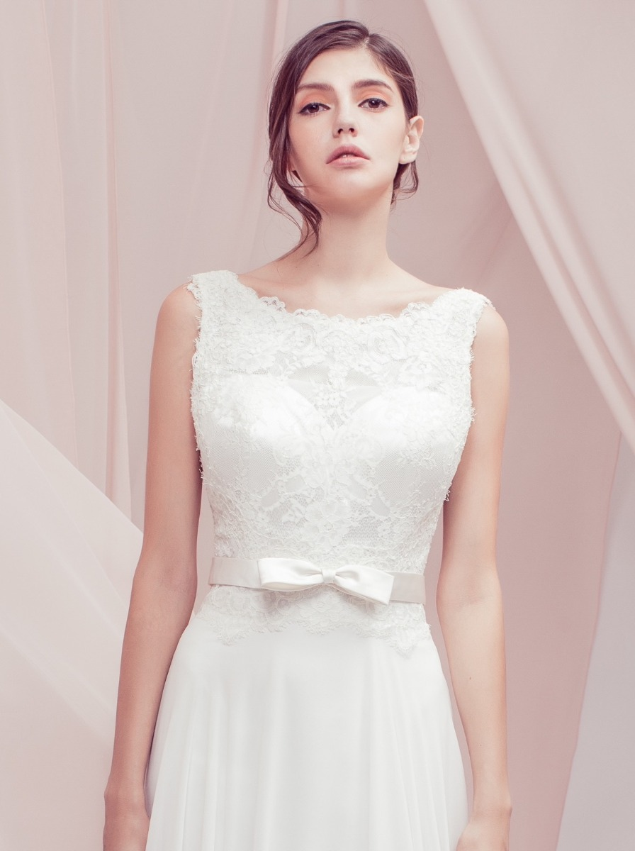Flowing chiffon wedding dress with a lace bodice and satin ribbon belt at the waist.
