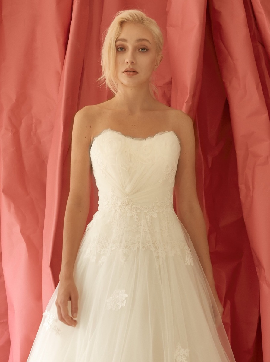 Princess wedding dress in tulle with a slightly draped bodice adorned with small ruffles along the neckline. Romantic floral lace appliques around the waist and cascades to the skirt.