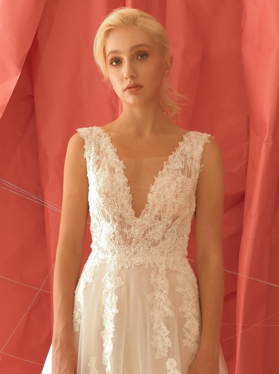 A-line wedding dress in tulle with beaded floral appliques over a V-neckline, embroidered tulle bodice.