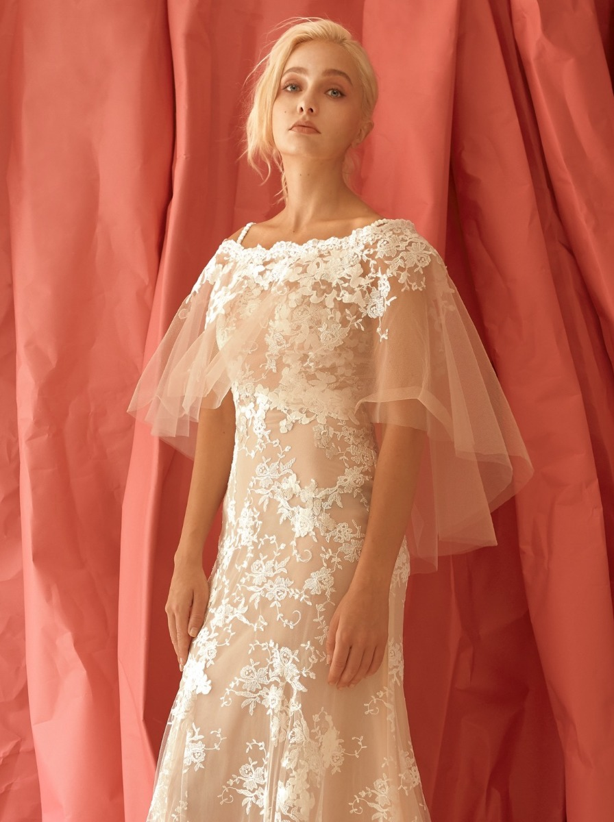 Mermaid wedding dress in nude colour with floral white lace appliques. Off-shoulder neckline with ruffle tulle cape front and back.