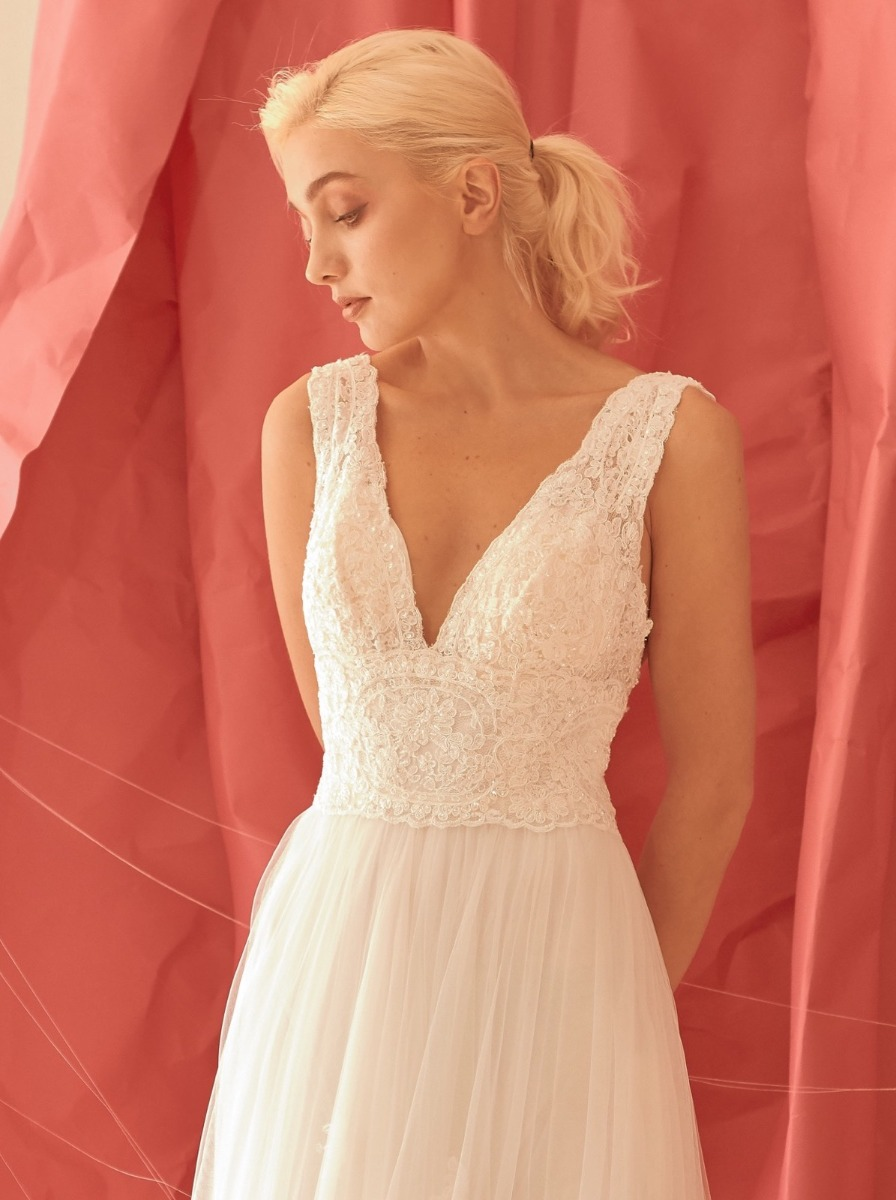 A-line wedding dress in tulle with beaded lace appliques over a V-neckline bodice.