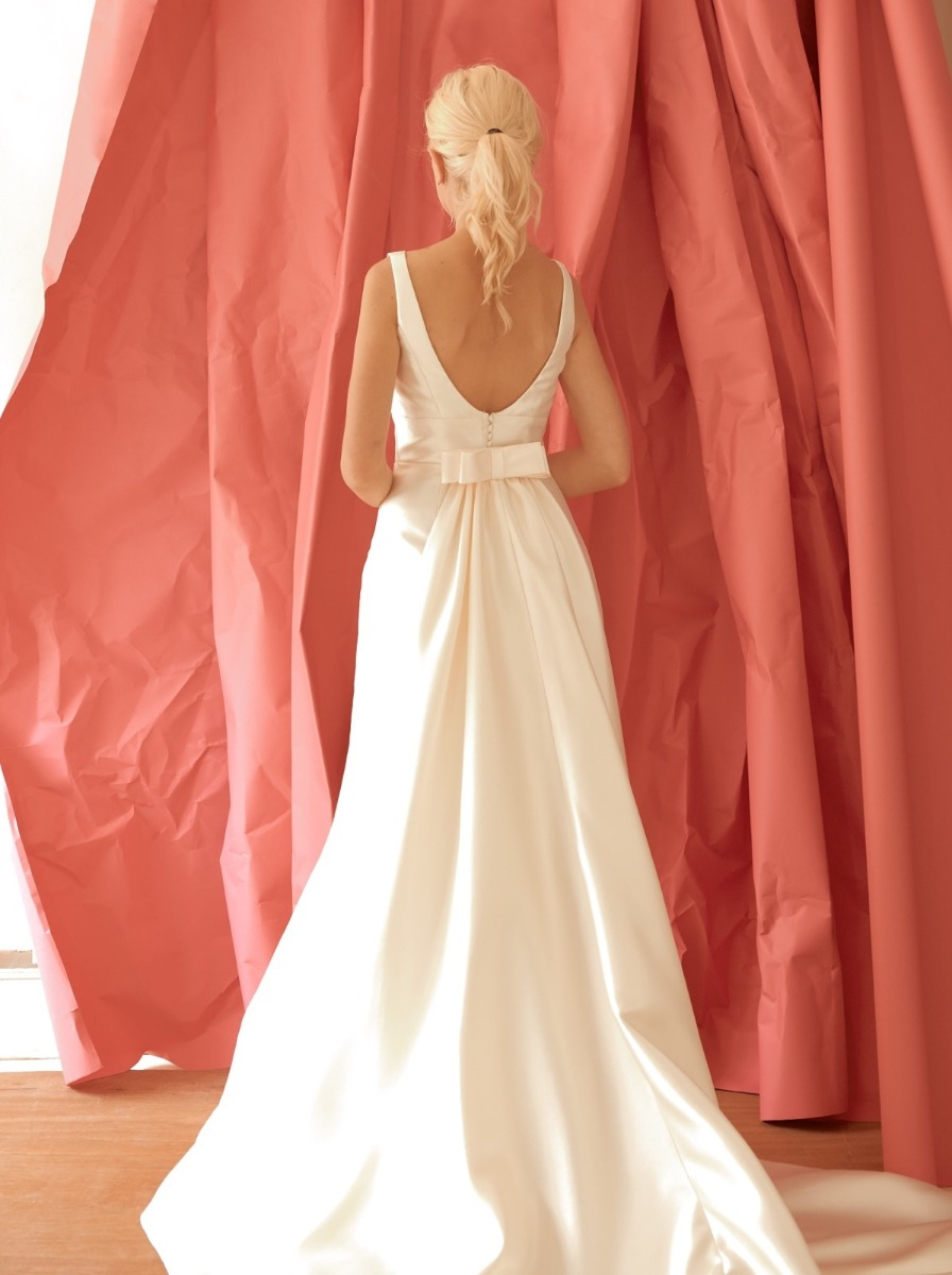 Open back with small bow at the back of the waist that flares out into a long train.