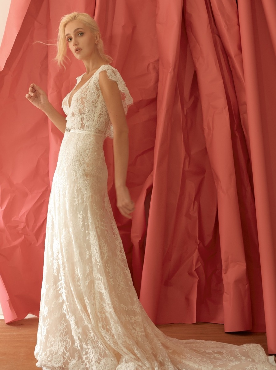 Column wedding dress in lace with glistening beaded floral appliques over a semi-sheer, V-neckline bodice. Waist with crystal gemstone applique and beaded satin thin belt.